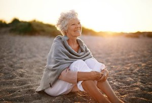 Older Pain-free Woman Sitting On The Beach