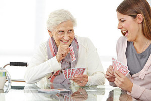 elderly woman playing cards with home care aide
