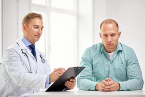 man being told by doctor he has prostate cancer.