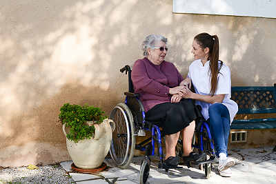 Elderly senior woman on wheelchair with aide