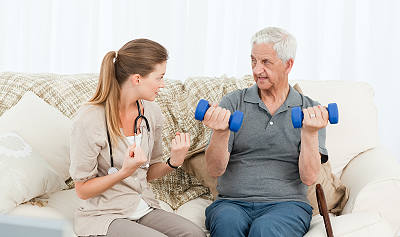 Elderly man exercising with aides help