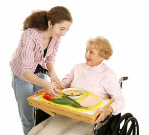 aide serving elderly woman a healthy meal