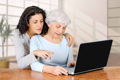 aide helping elederly woman with computer